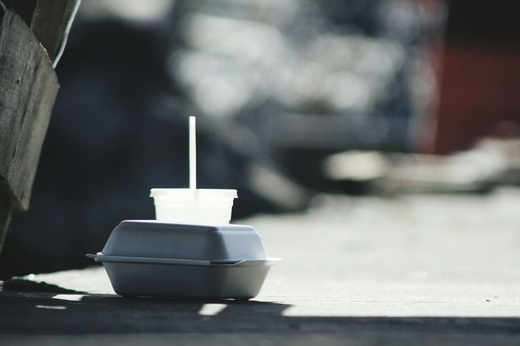 Disposable cup on table during sunny day