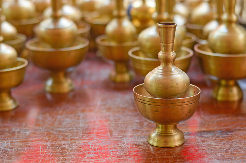Close-up of antique containers on wooden table