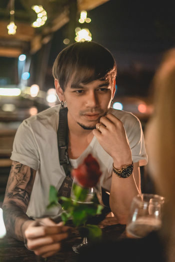 Young man sitting on table at restaurant