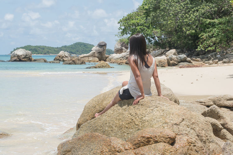 Rear view of woman on rock at beach against sky