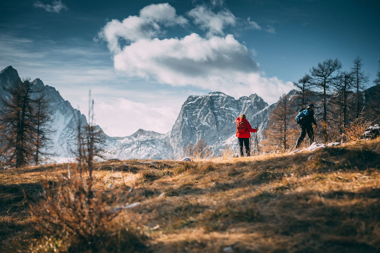 Group of hikers with backpack hiking along a trail towards mountain Adventure Backpack Beauty In Nature Cloud - Sky Cold Temperature Day Hiking Leisure Activity Lifestyles Men Mountain Nature Outdoors Real People Rear View Scenics Sky Snow Togetherness Two People Walking Winter