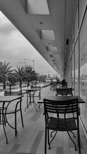 Empty chairs and tables in cafe against buildings