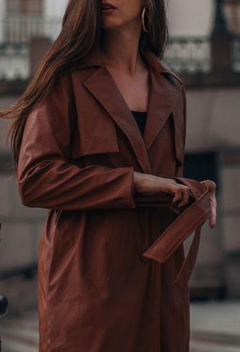 Autumn fashionable female outfit. stylish woman walking in brown coat outdoors. trendy modern