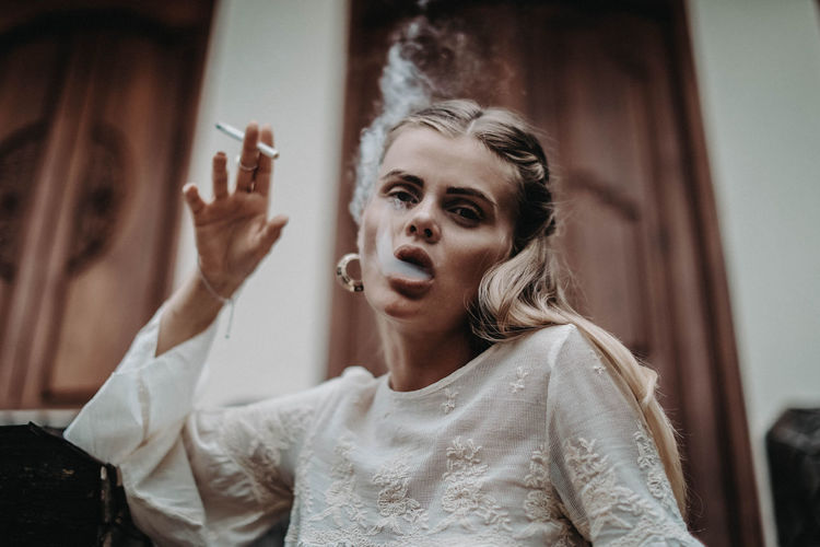Young hippie girl blonde with boho accessories smoking a cigarette and blowing smoke