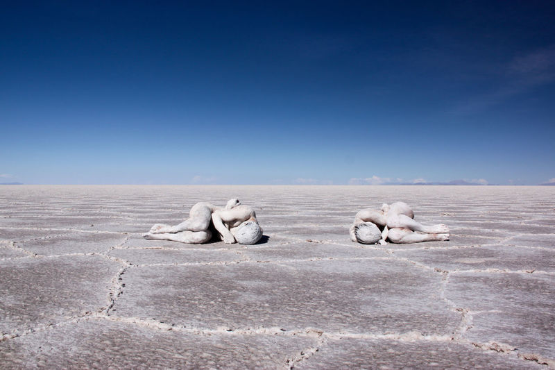 High angle view of sensuous naked man and woman covered with powder lying on barren land against clear sky