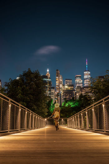 Man by illuminated bridge and buildings against sky at night
