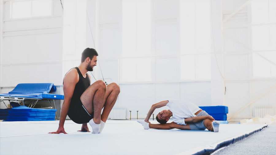 Full length of man and boy stretching