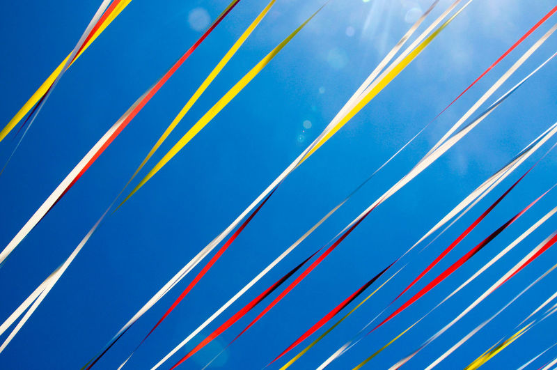 Low angle view of ribbon against blue sky