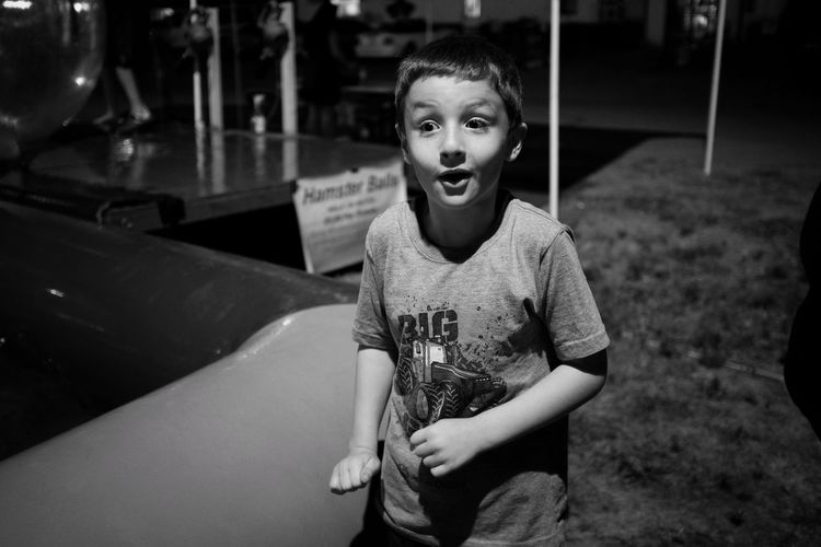 Boy standing on field gage county fair during night