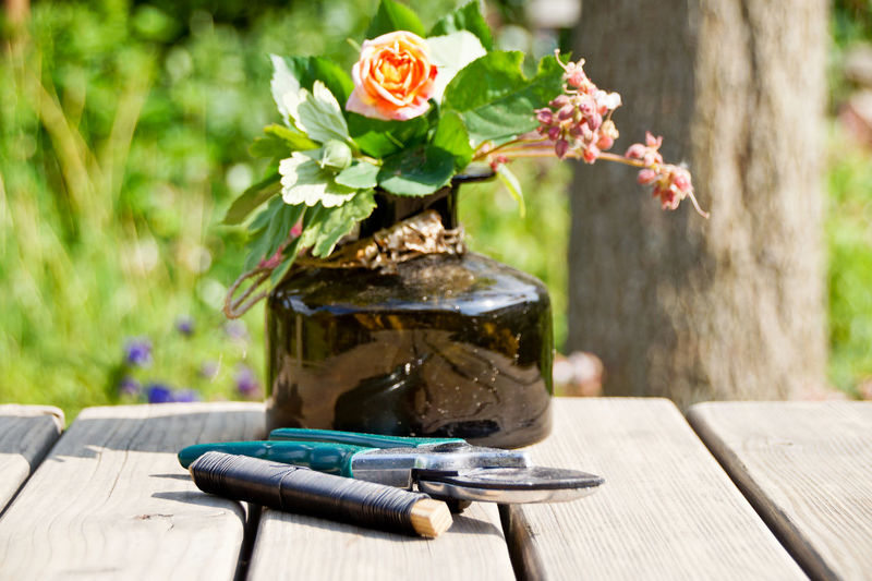Close-up of flower vase with string and pruning shears on wooden table