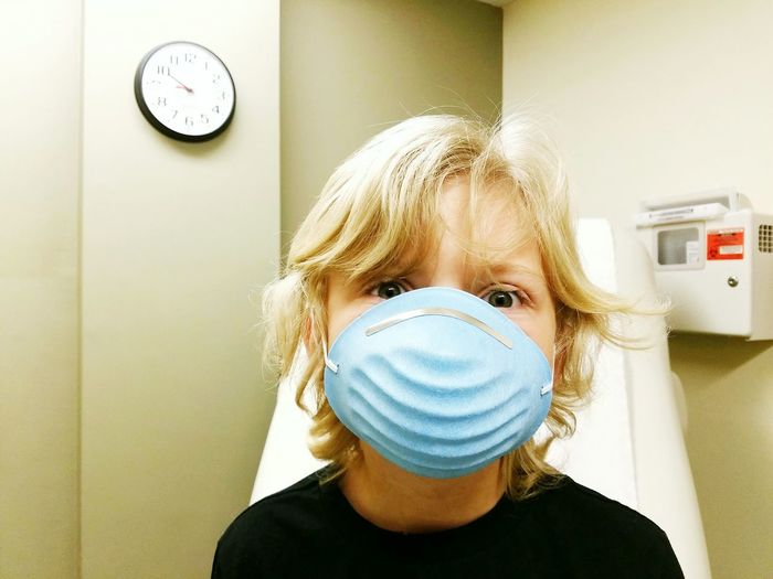 Close-up portrait of boy wearing surgical mask in clinic