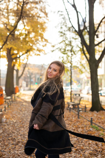 Portrait of smiling young woman against trees during autumn