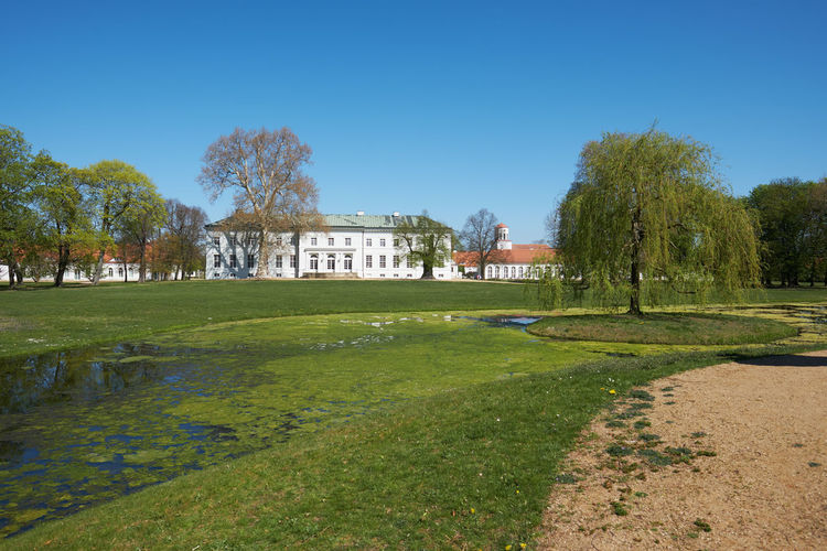 neuhardenberg palace and park against blue sky Plant Architecture Built Structure Tree Building Exterior Grass Sky Nature Green Color Building Mansion Day No People Clear Sky Water Growth Blue Outdoors Palace Copy Space Neuhardenberg Spring Oderbuch Brandenburg Schinkel Countrside Park Neuhardenberg Palace Springtime Spring Is Coming  Spring Is In The Air