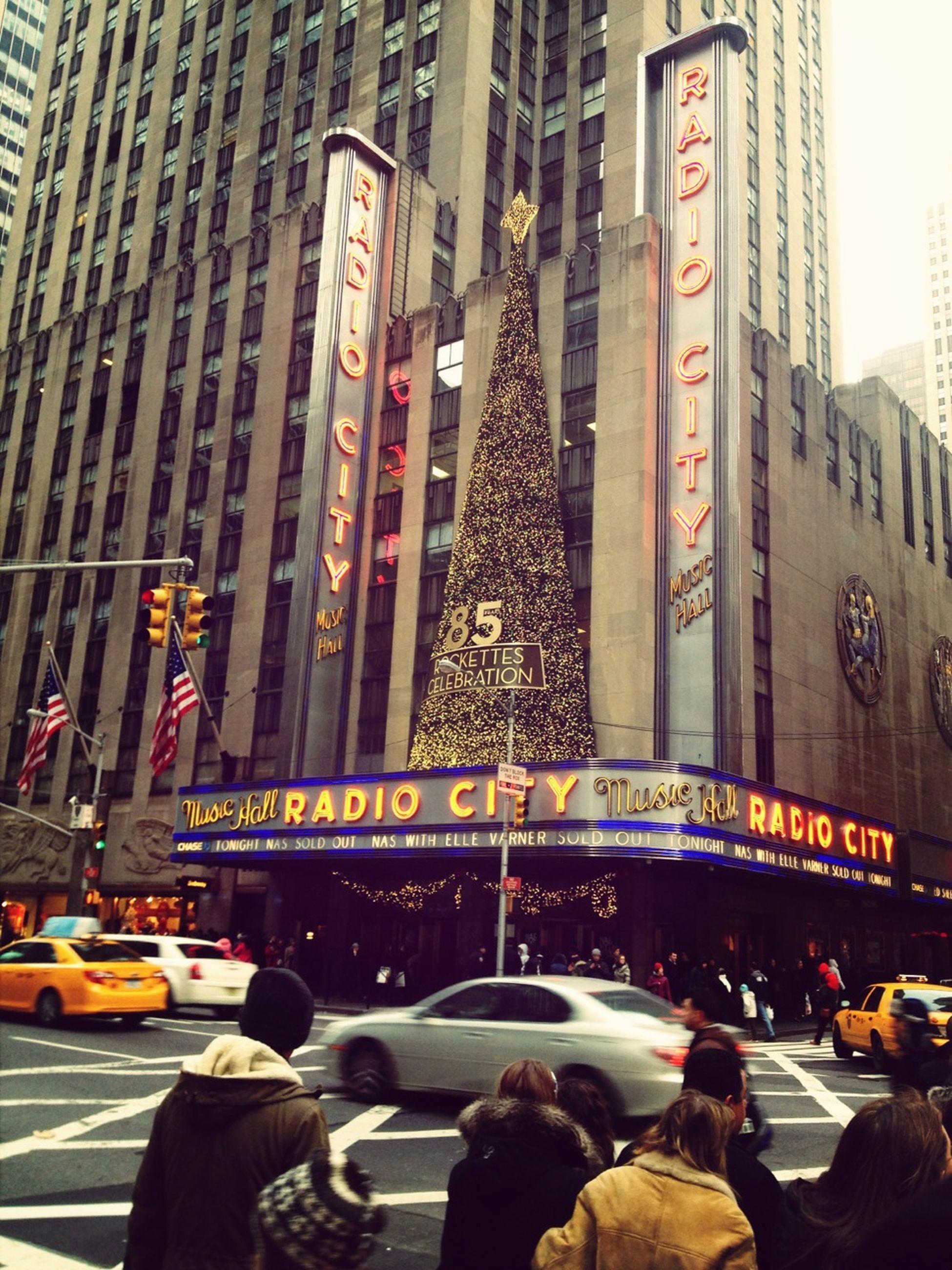 architecture, built structure, building exterior, city, large group of people, street, men, city life, person, lifestyles, city street, transportation, car, capital cities, leisure activity, road, travel destinations, crowd, famous place