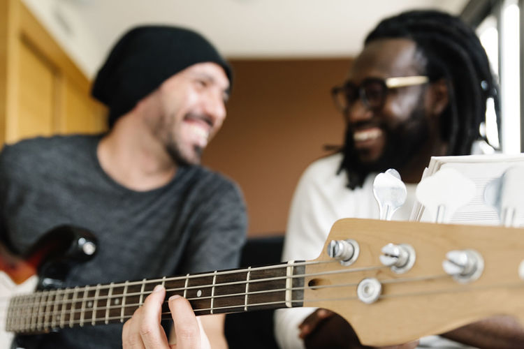Smiling man playing guitar by friend