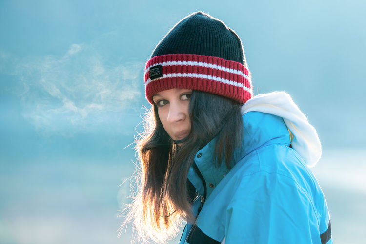 Portrait of young woman in hat against sky