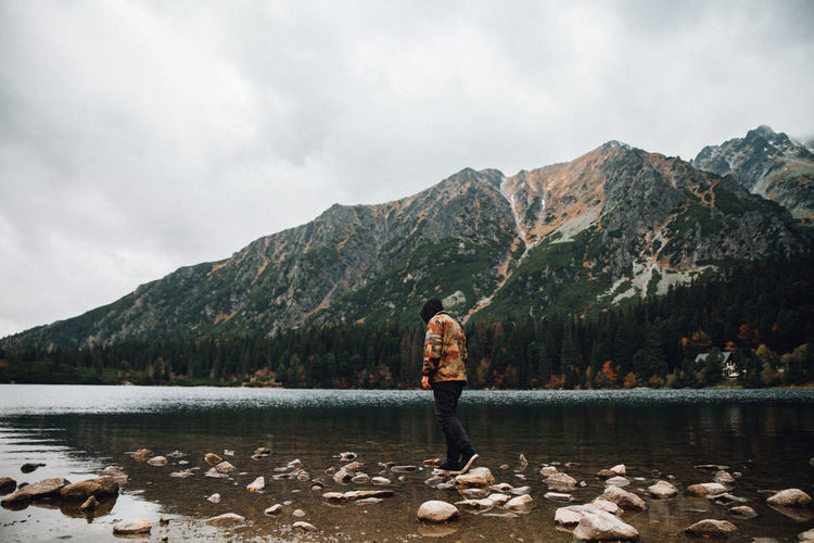 Rear view of man standing by lake against mountains