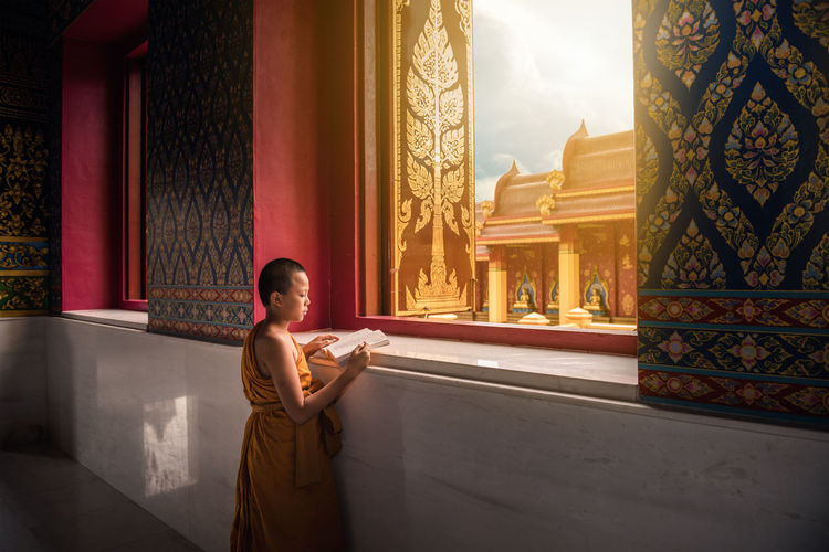 Portrait of little novice monk is reading a book in the temple. Architecture Religion Adult Young Adult Spirituality Belief Travel Destinations Women Built Structure Standing Building Tourism Indoors  Architectural Column History Place Of Worship Contemplation Monk  Architecture Art Buddah Reading Reading A Book Old