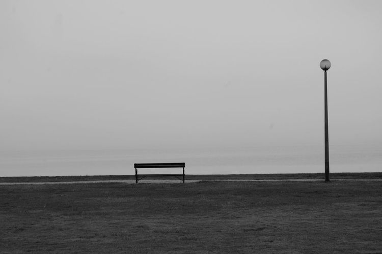 Bench on field by sea against clear sky