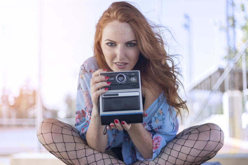 Portrait of woman holding instant camera