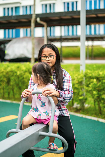 Portrait of sister playing with sibling at park