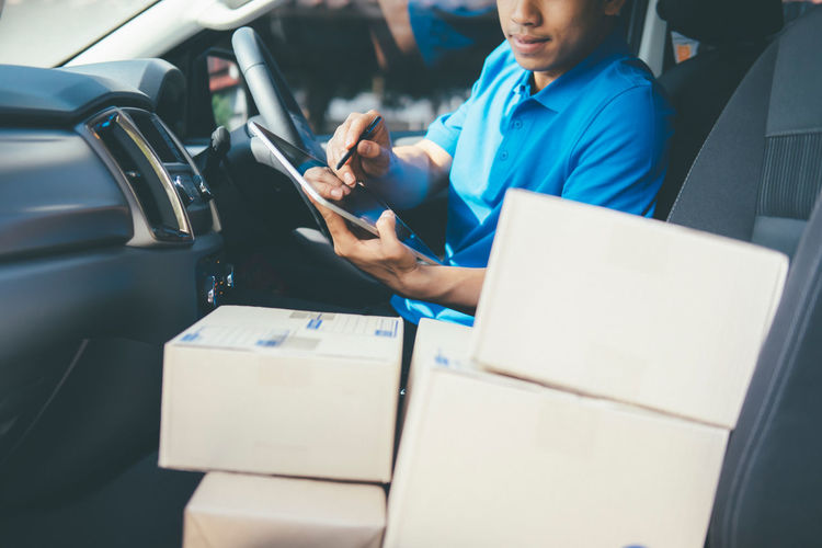 Midsection of delivery man with box sitting in car