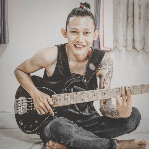 Portrait of a smiling young man playing guitar