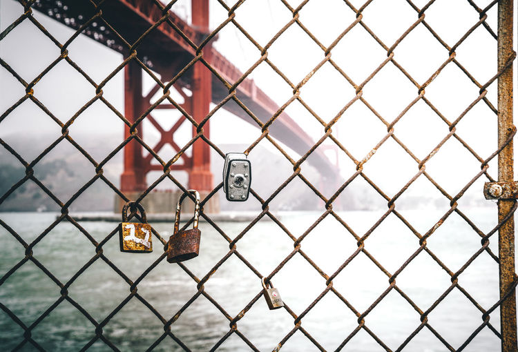 Locks on a fence California Cloudy Golden Gate Bridge Locks San Francisco Bridge Chainlink Fence Fence Focus On Foreground Lock Love Lock No People Outdoors Padlock Protection Security Selective Focus Water