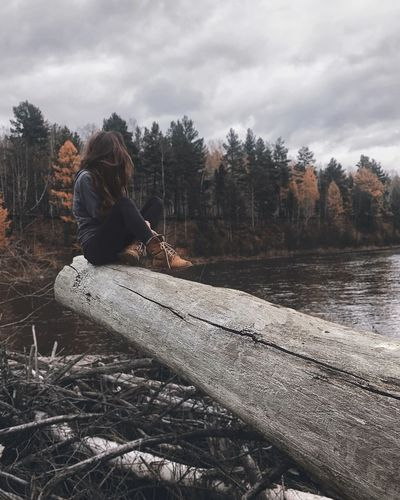 Woman Sitting On Log At Forest