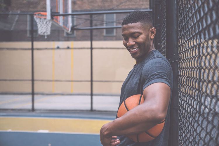 Smiling young man holding basketball by chainlink fence