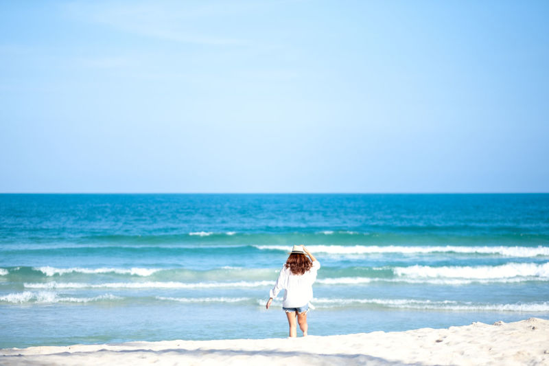 A woman strolling on the beach with the sea and blue sky background Adult Asian  Attractive Back Background Beach Beautiful Beauty Blue Clouds Coast Female Fresh Fun Girl Happiness Happy Hat Holding Holiday Lady Leisure Lifestyle Look Nature Ocean Outdoor People person Relax Relaxation Sand Sea Sky Space Standing Stroll Strolling Summer Sun
