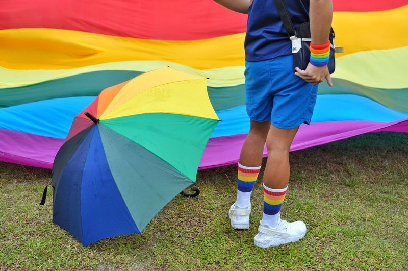 Low section of women with multi colored umbrella