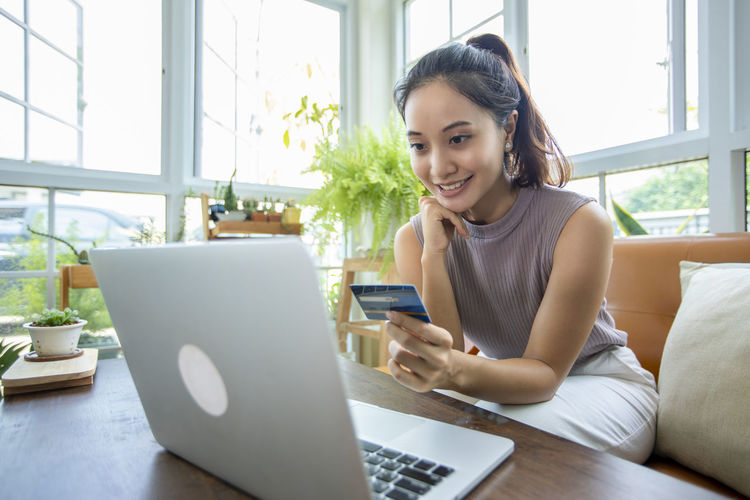 Young woman looking away while sitting on laptop