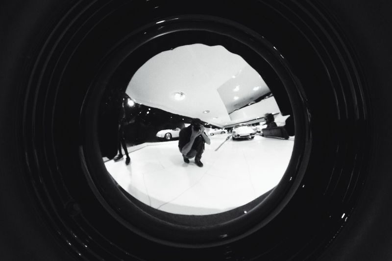 Reflection of people photographing in mirror