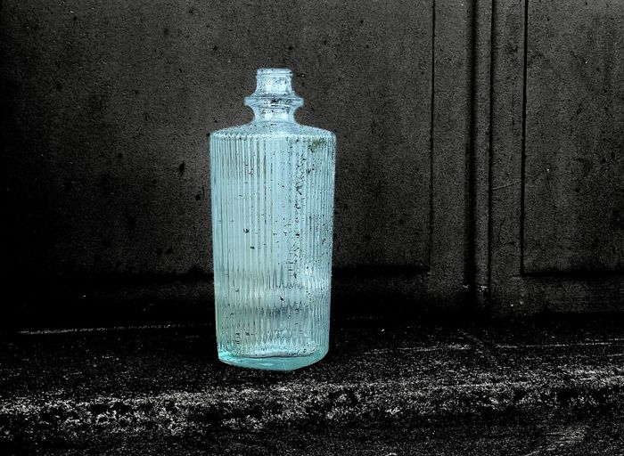 Close-up of old bottle on wall