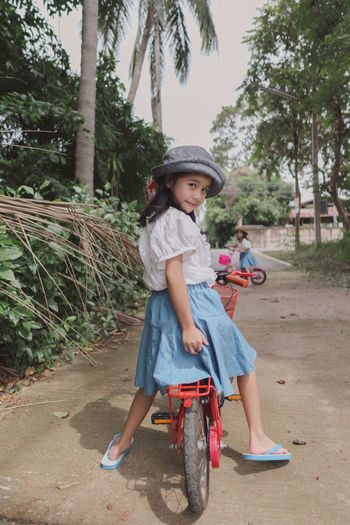 Full length portrait of cute girl riding bicycle on plants