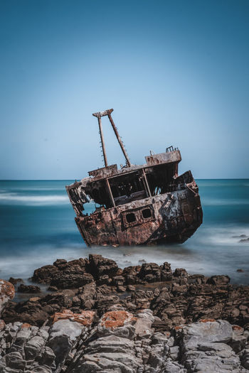 Shipwreck at beach against sky