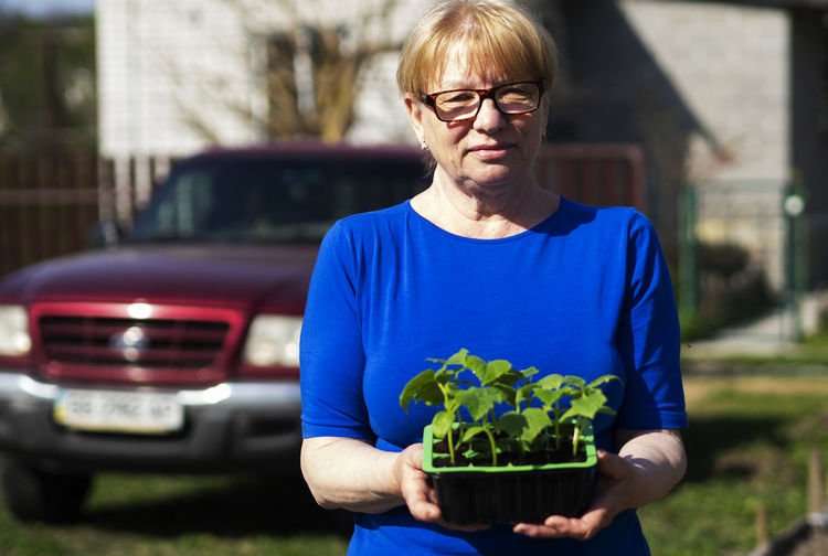 Senior caucasian woman is holds a container with cucumber seedlings. Seedlings Senior Women Caucasian Holds Container Cucumber Glasses Front View Eyeglasses  One Person Real People Focus On Foreground Waist Up Lifestyles Day Casual Clothing Mode Of Transportation Portrait Holding Mature Adult Looking At Camera Car Leisure Activity Women Outdoors Teenager Hairstyle