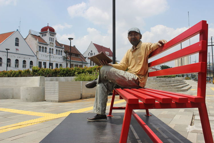 Man sitting on bench against buildings