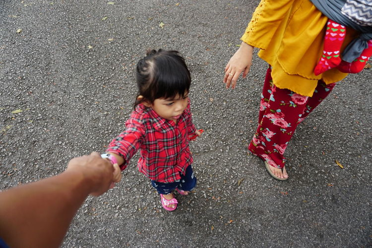 Cropped hand of person holding girl hand by woman on road