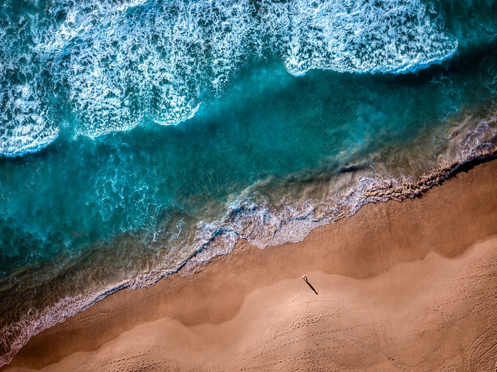 Morning walks at the beach Beauty In Nature Water Nature Land Sea Day Scenics - Nature Solid Geology Wave Sport High Angle View Rock Travel Destinations Power In Nature Outdoors One Person Aerial View Drone  EyeEm Best Shots Sand Ocean Shore 17.62°