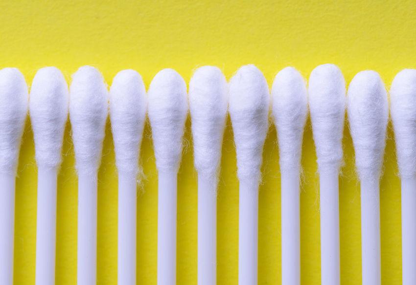 Multiple ear sticks over yellow background Hygiene In A Row Close-up Cosmetic Ear Stick Large Group Of Objects Macro Object Organized Overhead View Pattern Stick Studio Shot Swab Wax White Yellow
