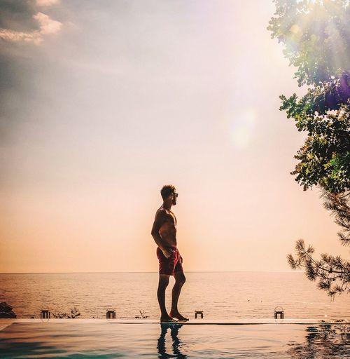Full length of man standing on infinity pool against sky during sunset