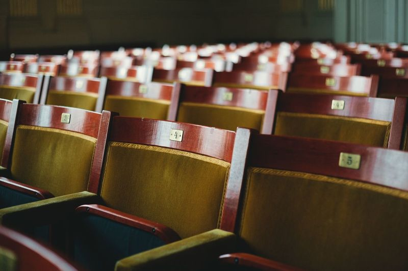 Empty wooden chairs with numbers in auditorium