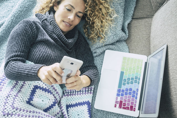 Curly woman with gray sweater lying on brown sofa and blue blankets relaxes watching and chatting with cell phone on a cold winter day - coloured keyboard laptop on her side Wireless Technology Connection Portable Information Device Technology Mobile Phone Smart Phone Communication One Person Young Adult Holding Real People Young Women Women Adult Lifestyles Using Phone Telephone Winter Leisure Activity Warm Clothing Outdoors Hairstyle Cold Temperature Caucasian Curly Hair Casual Clothing Blanket Sofa Lying Down Chatting Blogger Appliance Business Above Reading Modern Smiling One Woman Only Relaxation