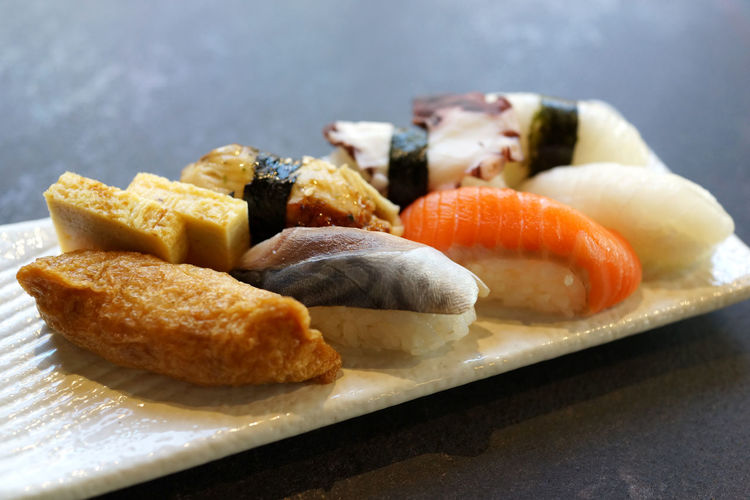 Assorted Japanese sushi on a white plate Food Ready-to-eat Freshness Indoors  Close-up Still Life Healthy Eating Japanese Food No People Sushi Seafood Plate Rice Table Focus On Foreground Wellbeing Serving Size Tray Snack Temptation