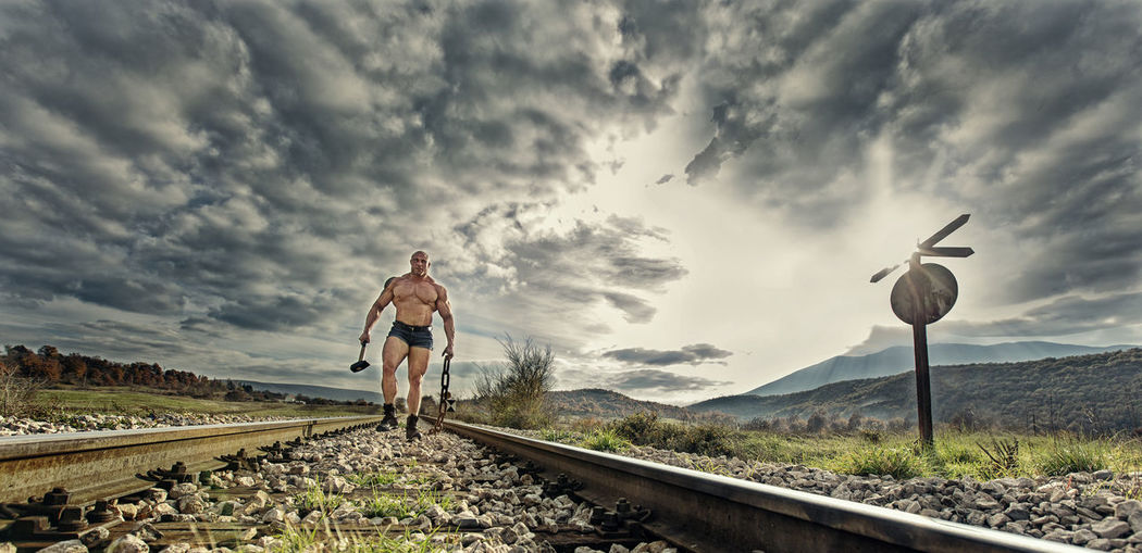 Hammer on the Railroad BodyBuilder Cloud - Sky Rail Transportation Railroad Track One Person Dramatic Sky Standing Outdoors Cloudscape Sledgehammer Man Male Strong Railroad Crossing Sky Transportation