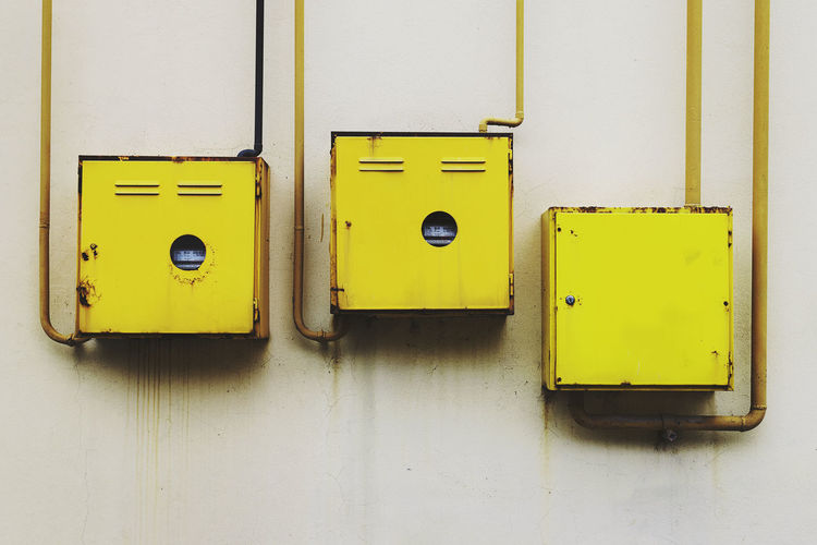 Three yellow rusty metal wall lockers for natural gas mounted on the wall Abstract Photography Gauges Industrial Photography M Natural Gas Pipes And Valves Close-up Connection Day Energy Distribution Gas Station Metal Closet Natural Gas Pipes No People Outdoors rule of thirds Rusty Metal Stained Streetphotography Technology Wall Locker Wall Stains Yellow Yellow Color Yellow Metal Structure