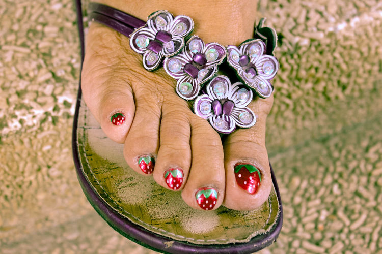 Low section of woman wearing floral flip-flop