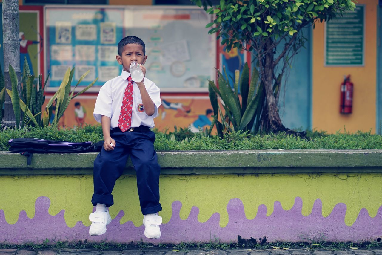 School Boy Drinking Water While Sitting On Retaining Wall
